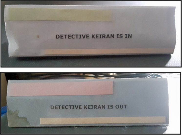 Photograph of two signs indicating whether Keiran is at her desk, or not